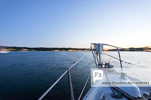 Segelboot segelt auf See gegen klaren Himmel