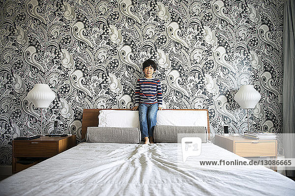 Boy standing on bed against wall in bedroom