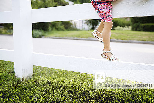 Low section of girl climbing on fence