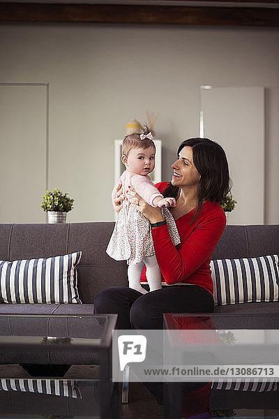 Happy mother holding baby daughter and sitting on sofa at home