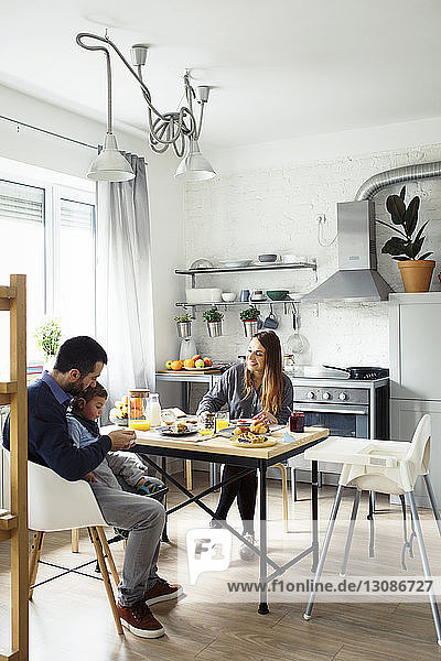 Parents with son having breakfast at table in kitchen