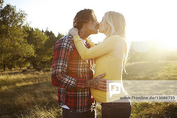 Romantic couple kissing while standing on grassy field during sunny day