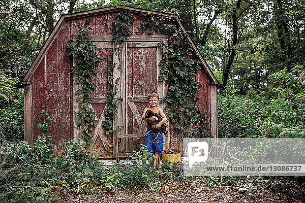 Shirtless boy carrying hen while standing against cottage in forest