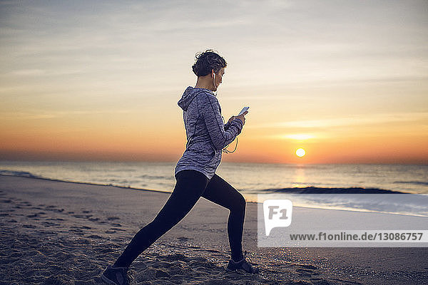 Woman exercising while listening music at beach against sky