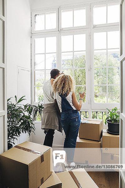 Rückansicht eines Paares  das durch ein Fenster schaut  während es in seinem neuen Zuhause steht  durch eine Tür