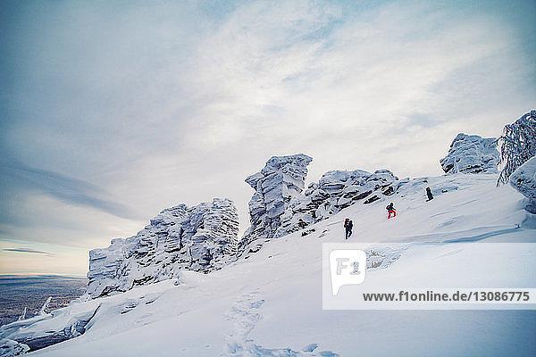 Wanderer erklimmen schneebedeckte Berge gegen wolkigen Himmel