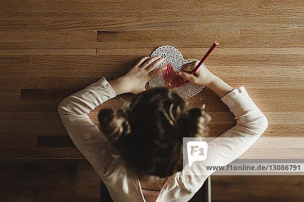 Draufsicht eines Mädchens  das zu Hause eine Valentinskarte auf den Tisch legt