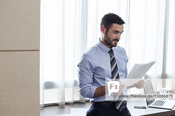 Geschäftsmann liest Dokumente  während er im Hotelzimmer am Fenster steht