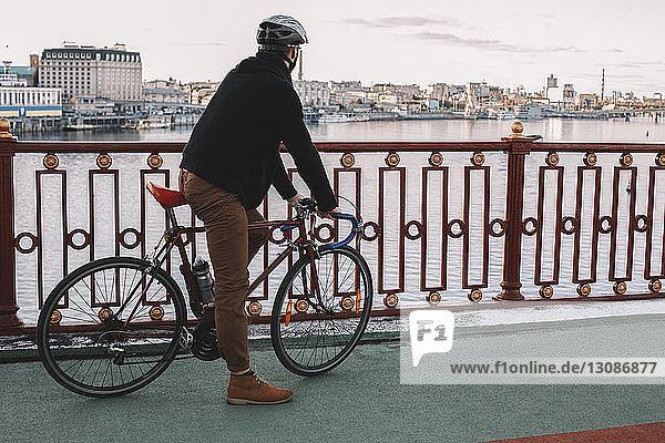 Seitenansicht eines männlichen Radfahrers mit Fahrrad  der auf einer Brücke über den Fluss gegen den Himmel in der Stadt steht