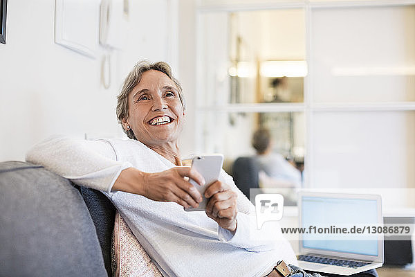 Cheerful mature woman holding smart phone while sitting on sofa at home