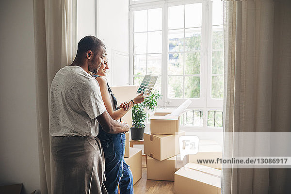 Couple looking at color swatch while leaning by wall at new home