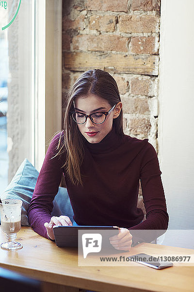 Woman using tablet computer while sitting in cafe