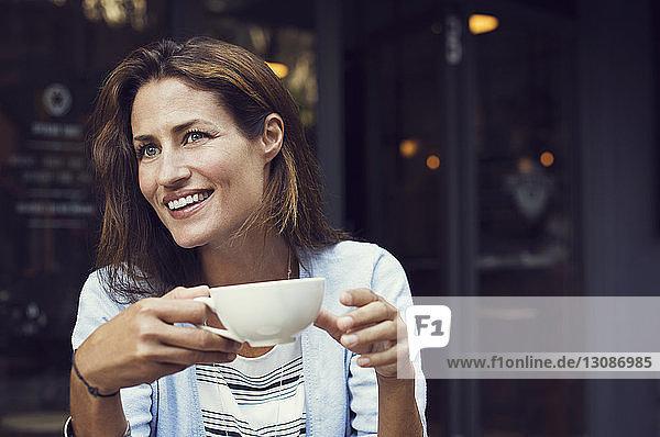 Glückliche Frau schaut weg  während sie im Straßencafé eine Kaffeetasse hält
