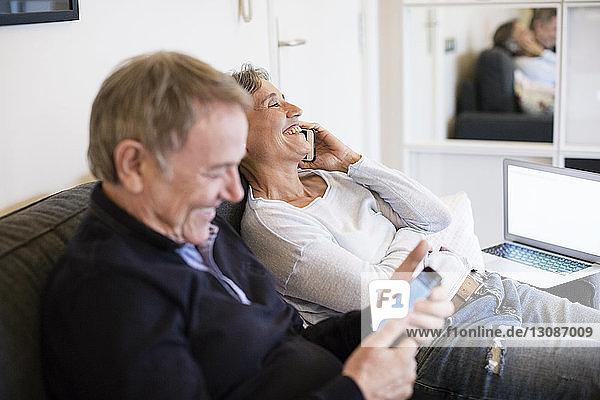 Glückliches älteres Ehepaar benutzt Smartphones im Wohnzimmer