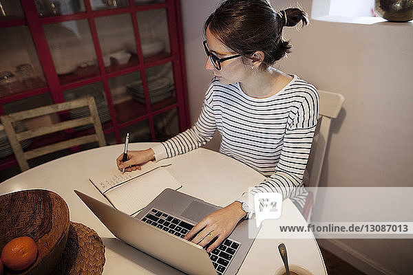 Woman planning while working on laptop at home