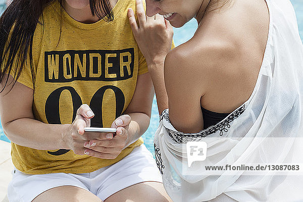 Ein Teil der Frauen benutzt Smartphones am Pool
