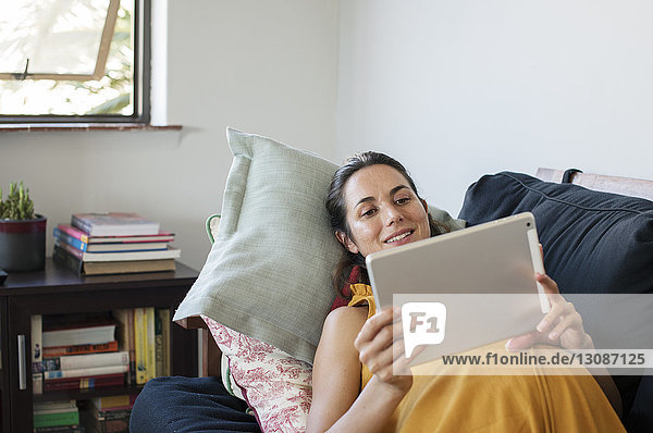 Schwangere Frau benutzt Tablet-Computer,  während sie zu Hause auf dem Sofa liegt