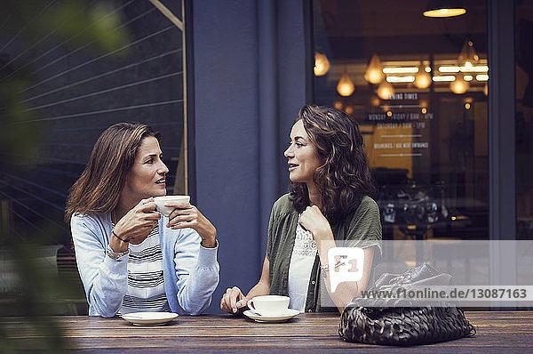 Freundinnen unterhalten sich bei einem Kaffee im Straßencafé