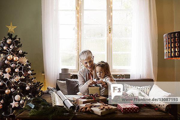 Großmutter hilft Mädchen beim Packen von Geschenken zu Weihnachten