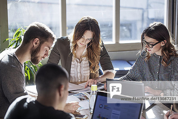 High angle view of college students studying while sitting at table in classroom
