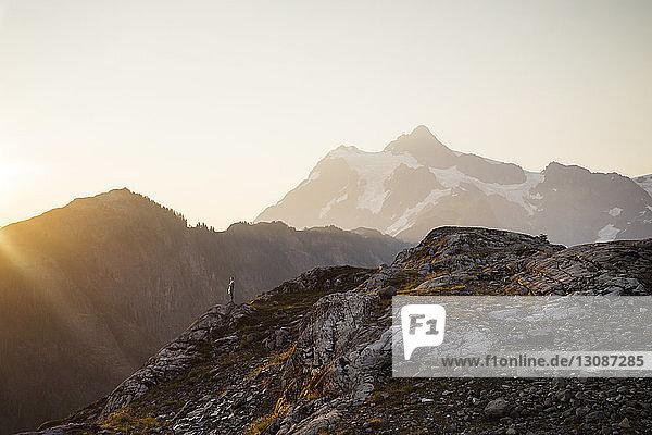 Frau steht bei Sonnenuntergang auf Klippe gegen Berge