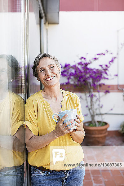 Portrait of happy mature woman holding coffee mug while standing at porch