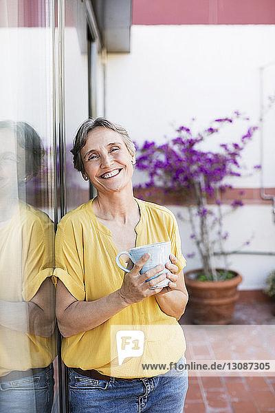 Porträt einer glücklichen  reifen Frau  die eine Kaffeetasse hält  während sie auf der Veranda steht