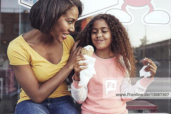 Mutter sieht ein Mädchen an  das Eiscreme genießt  während es auf dem Bürgersteig sitzt