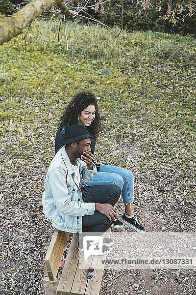 Hochwinkelaufnahme eines glücklichen Paares auf einer Parkbank sitzend