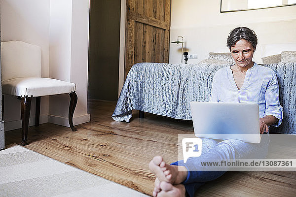 Mature woman using laptop while sitting on floor in bedroom