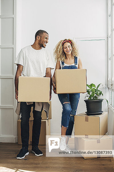 Happy couple carrying cardboard boxes while standing on floor at new house