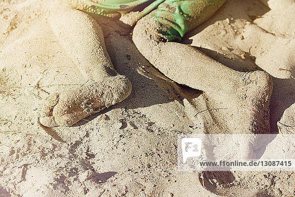 Unordentliche Beine eines Jungen  der am Strand im Sand liegt