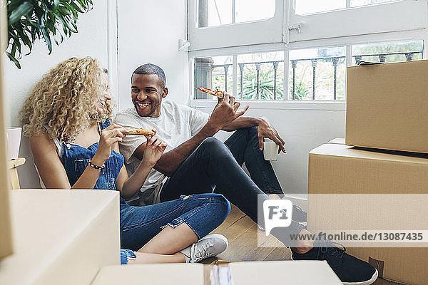 Glückliches Paar unterhält sich beim Pizzaessen an der Wand im neuen Haus