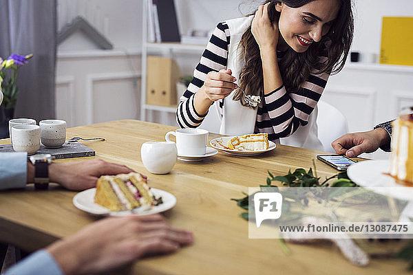 Glückliche Frau schaut auf Smartphone  während sie mit Freunden in der Party sitzt