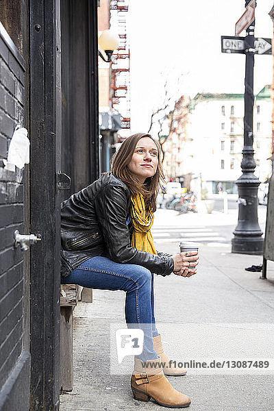 Seitenansicht einer Frau  die Kaffee hält  während sie auf einem Sitz an einem Gebäude in der Stadt sitzt