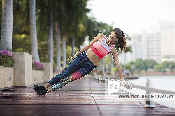 Woman performing side plank exercise on wooden walkway by river