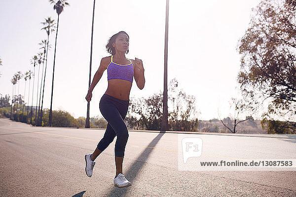 Frau joggt an einem sonnigen Tag auf der Straße