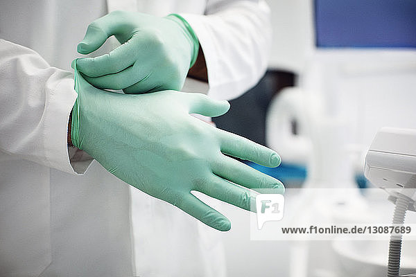Midsection of doctor wearing surgical gloves in clinic