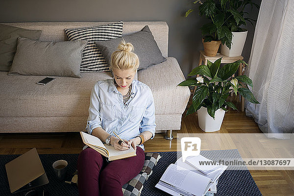 High angle view of woman writing in diary in living room