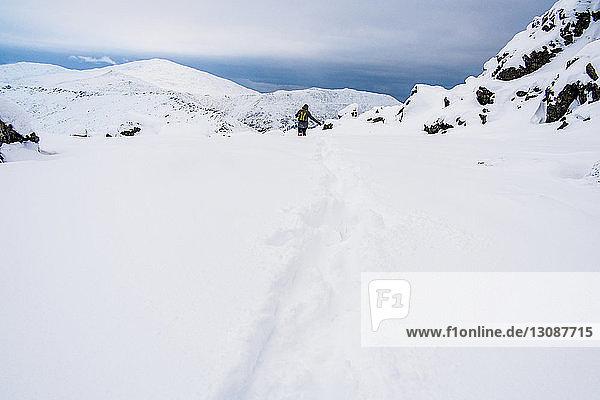 Fernansicht eines Wanderers auf einem schneebedeckten Berg gegen den Himmel