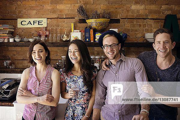Porträt von glücklichen Freunden  die vor der Küchentheke stehen