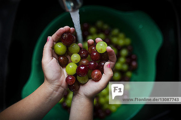 Cropped image of girl washing grapes in sink