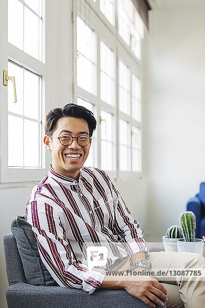 Portrait of happy businessman sitting on chair against windows in office