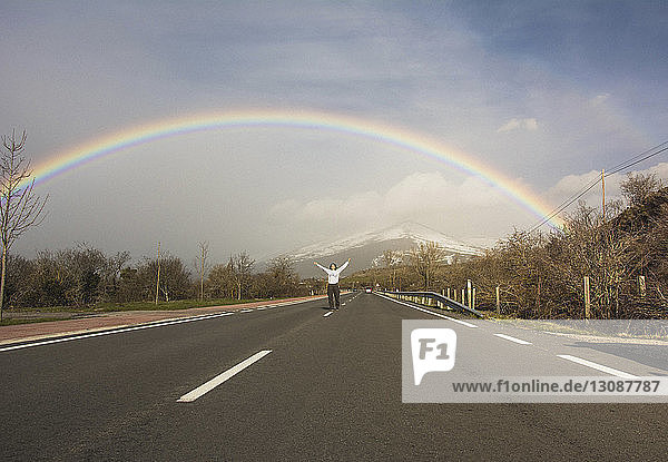 Mid distance view of young woman with arms raised standing on road against rainbow and cloudy sky during winter
