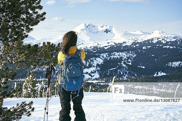 Rückansicht einer Frau  die auf einem schneebedeckten Feld steht