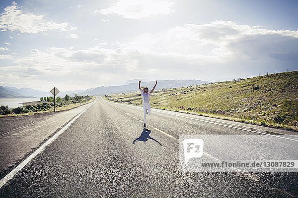 Glückliche Frau rennt an einem sonnigen Tag mit erhobenen Armen auf der Straße