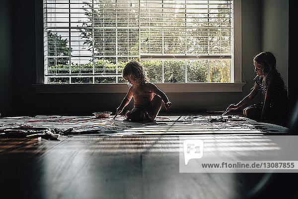 Schwestern malen  während sie zu Hause auf dem Boden am Fenster sitzen