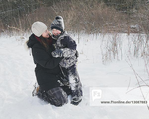 Fröhliche Mutter und Sohn auf verschneitem Feld