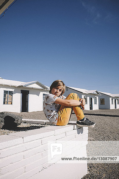 Full length of boy hugging knees while sitting on retaining wall against houses and clear sky during sunny day