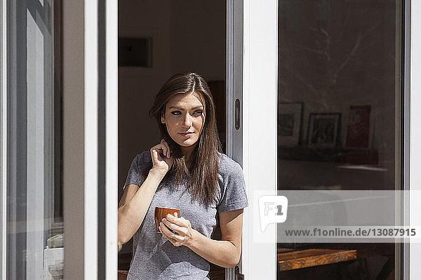 Schöne Frau hält Kaffeetasse und steht am Fenster